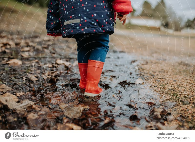Low section child with red rubber boots walking on puddle Puddle Rubber boots Red Child childhood Authentic Playing Exterior shot Autumn Dirty Day Water Wet