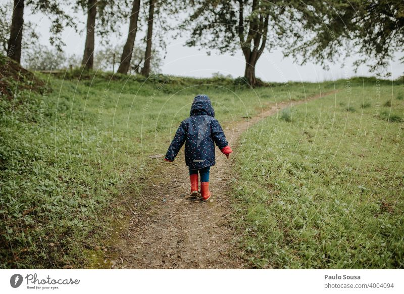 Rear view child walking in the park Child Red Rubber boots Walking Hiking Park woods Forest Authentic Infancy Playing Colour photo Boots Autumn Nature Joy Day