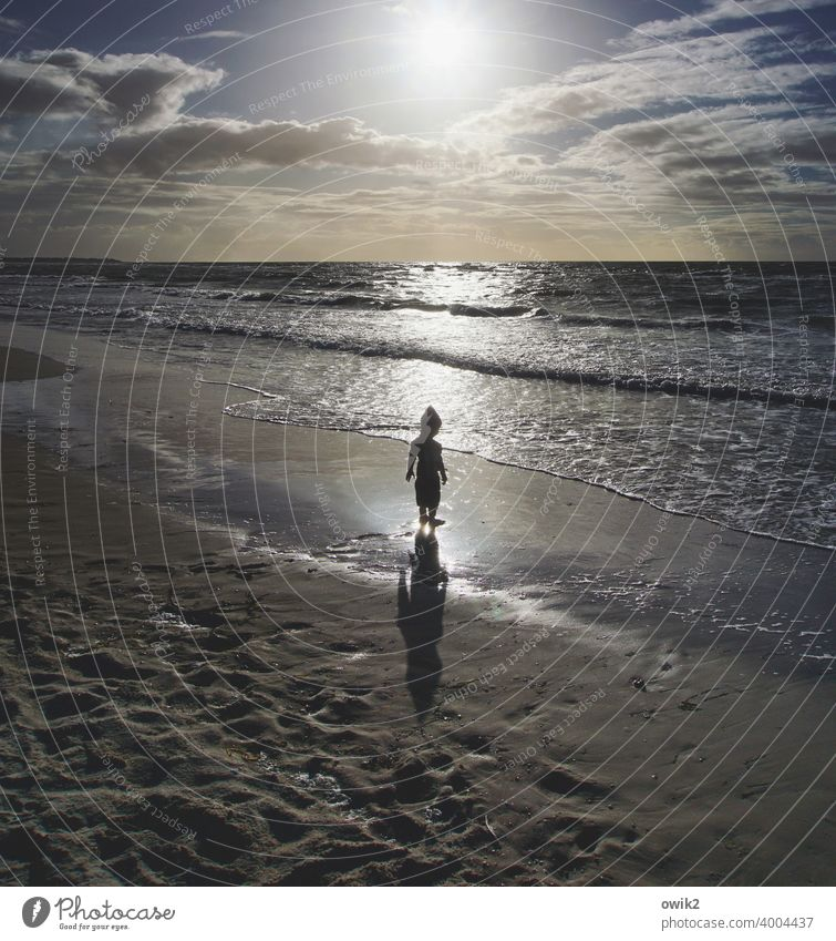 Youth philosophizes Beach luminescent Sun Back-light Water Sand Child Boy (child) Silhouette Shadow Contrast Stand Marvel 3-4 years Waves Lonely