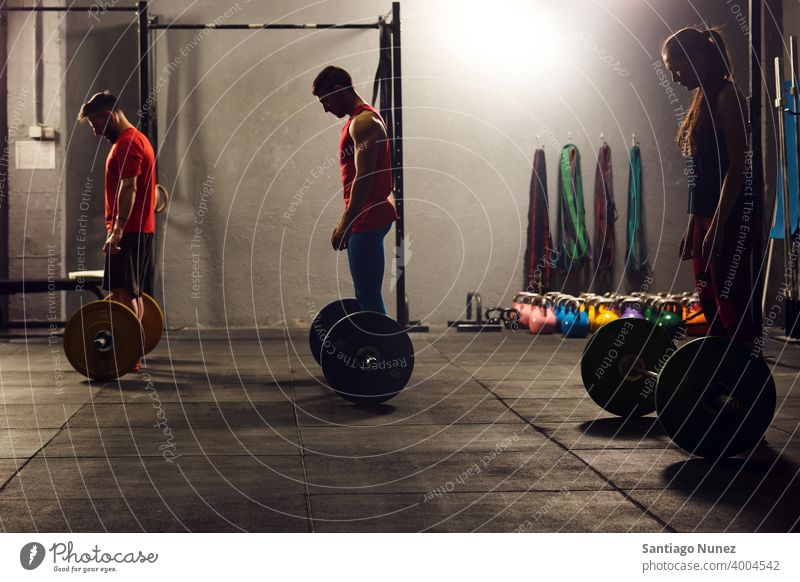 Three adults ready to lift barbells. crossfit functional training gym health sport fitness workout exercise lifestyle healthy people room isolated athletic male