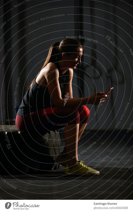 Woman sitting down and using smartphone. crossfit functional training gym health sport fitness workout lifestyle healthy adult sportswear equipment room