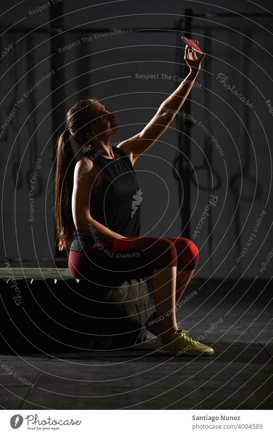 Woman sitting down and taking a selfie. crossfit functional training gym health sport fitness workout lifestyle healthy adult vitality sportswear room isolated