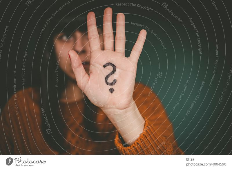 A woman holds up her hand, which has a question mark painted on it. Question mark Perplexed disorientation Identity insecurity Irritation Ask Insecure