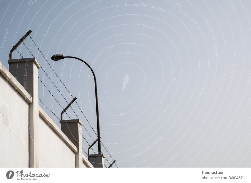 Wall with barbed wire and floodlights Wall (barrier) prison wall Barbed wire fence Wall (building) Sky penned Surveillance guarding Captured jail Protection