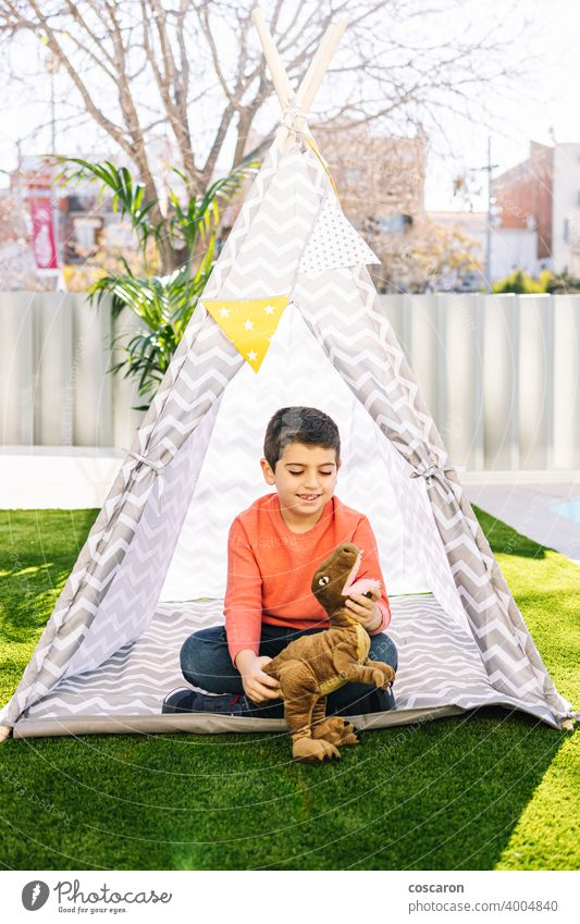Little boy playing in a indian tent caucasian child childcare childhood clothes costume cute dinosaur educational feather fun funny game garden grass happiness