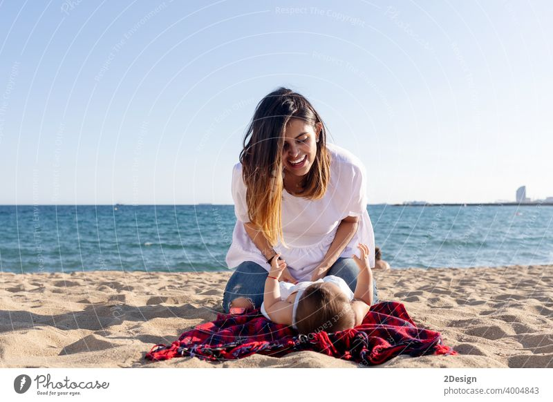 Smiling mom playing with newborn lying on beach towel baby love mother family happiness woman person smiling laughing sand sunlight together happy little summer