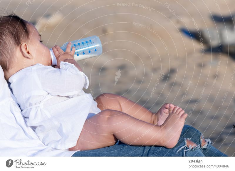 Newborn drinking milk from a baby bottle, sitting on mom legs outdoors newborn child infant mother healthy care cute person feeding childhood little white