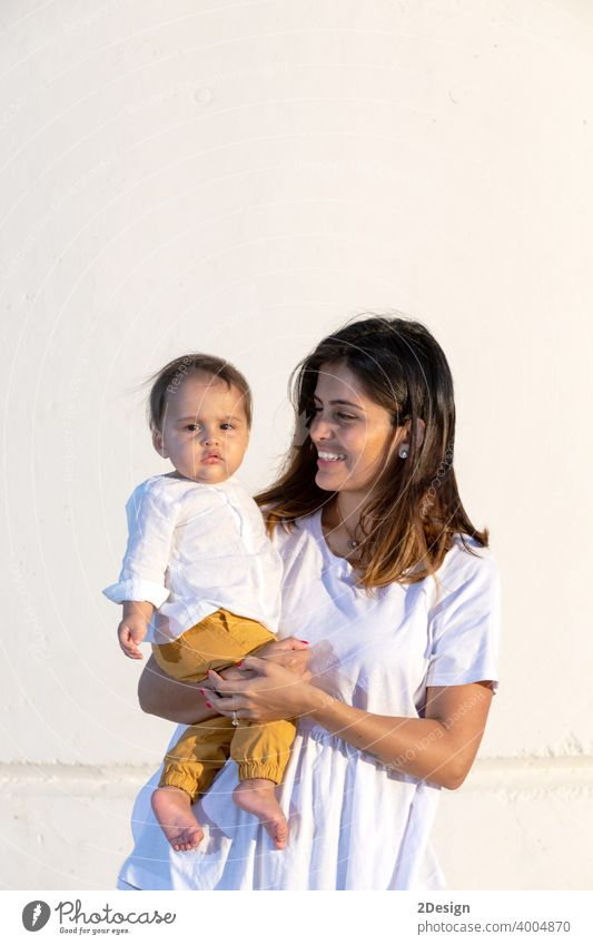 Young mother holding her little baby against white wall in sunny day child newborn love family woman care motherhood young childhood cute person happy girl