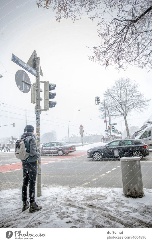 Man waits in snowstorm at busy intersection Winter Snow White cross urban Town Freeze Ice Cold Snowfall Snowflake Traffic light Transport Exterior shot Frost