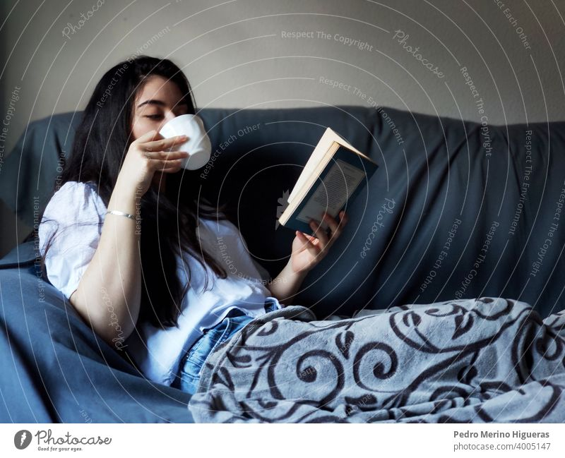 Woman drinking from a cup of coffee and reading a book female relax warm soft cute rest beautiful happy young living woman interior relaxation window people