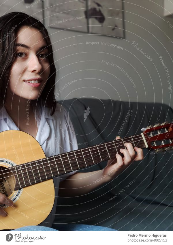 Woman playing the guitar on a gray sofa caucasian musical woman musician girl instrument background casual attire string studio young learning acoustic teenage