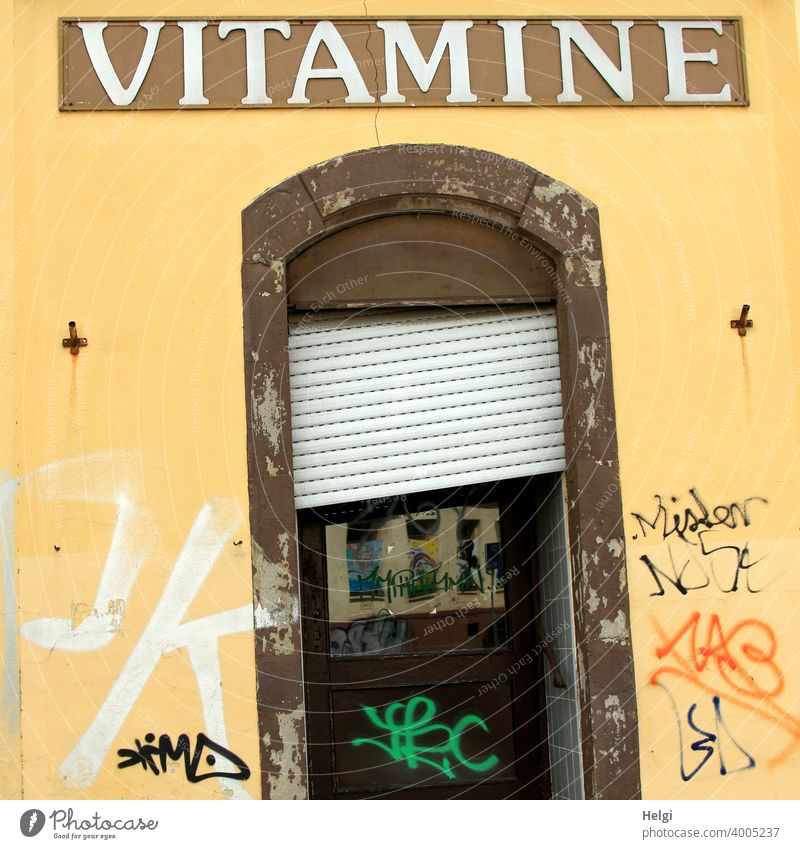 crooked and crooked - dilapidated entrance door with crooked blinds in yellow wall with graffiti and the writing VITAMINE above the door Wall (building) Facade