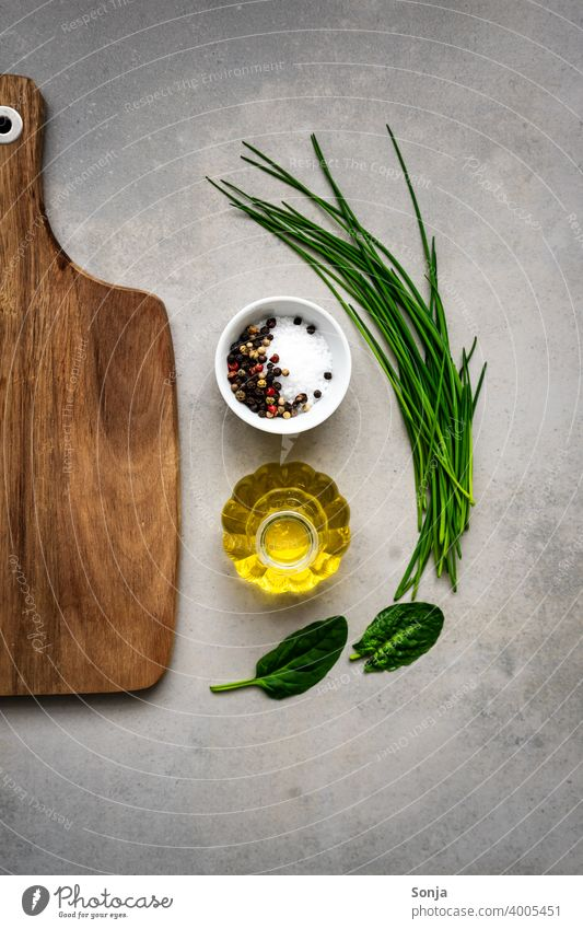 Fresh herbs, olive oil, salt and an empty wooden chopping board on a rustic table. Herbs and spices Chopping board Wood Empty Olive oil Salt Ingredients Food