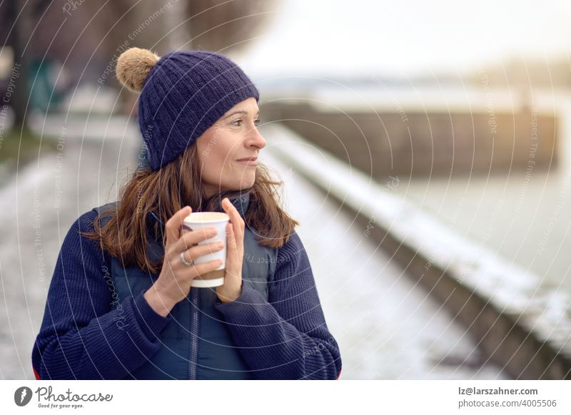 Happy middle-aged brunette woman going for a walk and drinking a coffee to go beverage outdoors tea female mature lifestyle generation european attractive mom