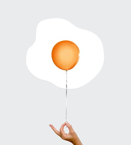 fried egg balloon Egg Yolk yolk thread color photograph To hold on Fingers Hand stop Orange Fried egg sunny-side up nobody Copy Space symbol picture
