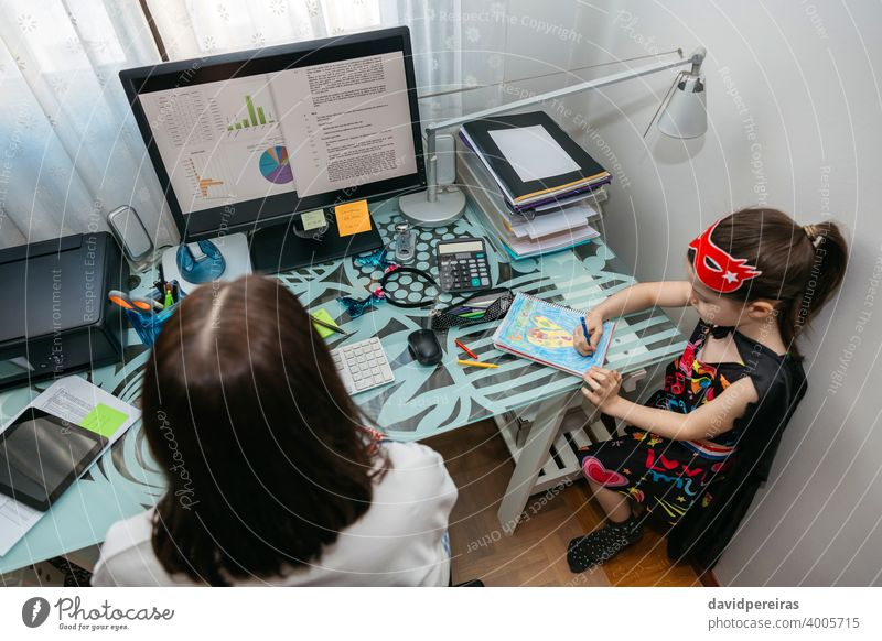 Woman teleworking with her daughter drawing overhead woman coronavirus covid-19 quarantine confinement computer top view family work reconciliation epidemic