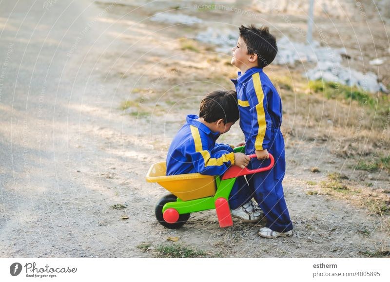 cheerful and smiling children are having fun in the field with a pushcart brothers siblings twins happy smile friendship elementary primary babies kid toddler
