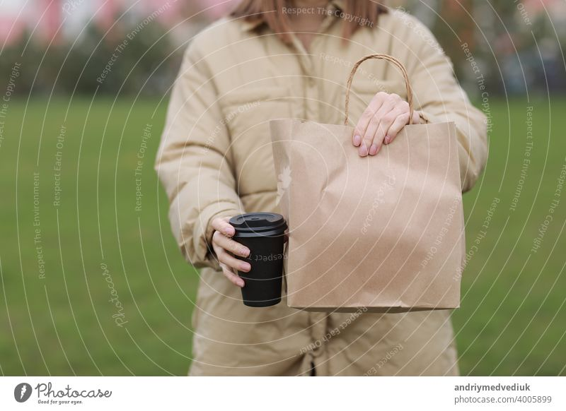 Takeaway cup with coffee, mock up for identity branding. Close-up of paper bag and paper cup in female hand.Young woman carries shopping bags and coffee.