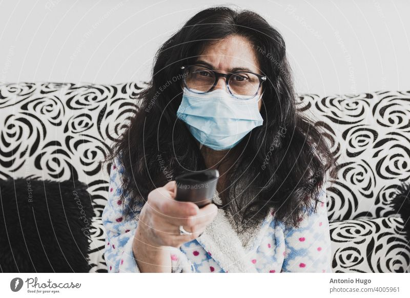 Middle-aged woman sitting on sofa with face mask and dressing gown changing channels with TV remote control. middle home television pandemic corona virus