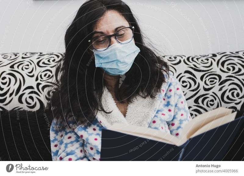 Middle-aged woman with face mask and dressing gown. Sitting on the couch and reading a book middle aged masked sitting sofa home quarantine virus corona