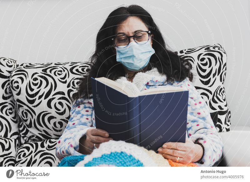 Middle-aged woman with face mask and dressing gown. Sitting on the couch and reading a book middle aged masked sofa home quarantine virus corona eyeglasses