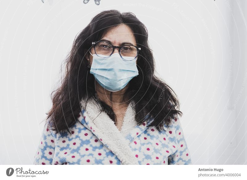 Portrait of a middle-aged woman with face mask isolated at home. portrait middle aged gown virus looking out window corona pandemic quarantine epidemic care