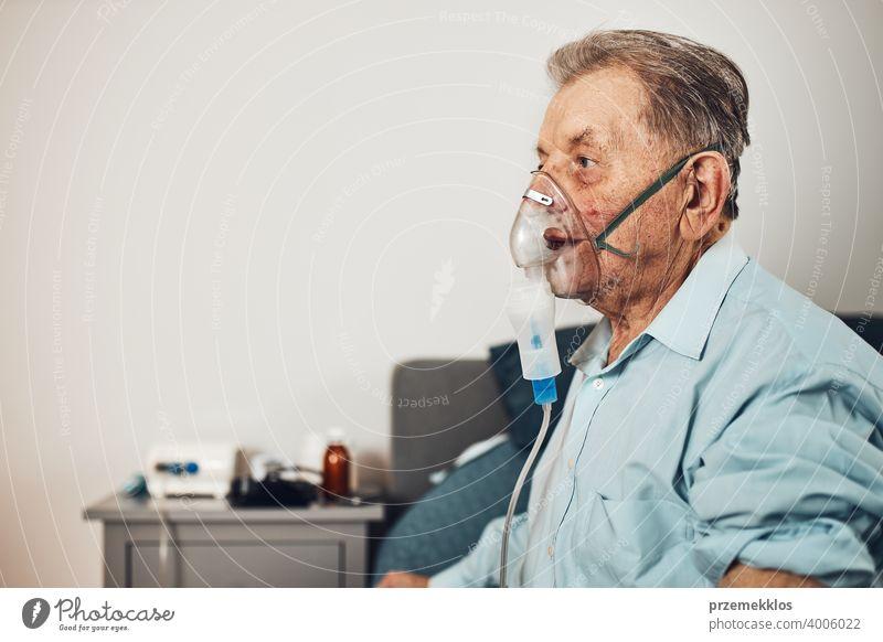 Senior man inhaling airways and lungs applying medicine. Covid-19 or coronavirus treatment. Man breathing through face mask using nebuliser patient person