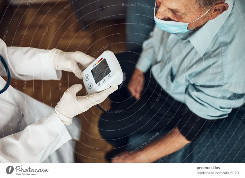 Doctor carying out blood pressure test and heart rate of senior man. Checking health condition elder patient suffering from arterial hypertension nurse check