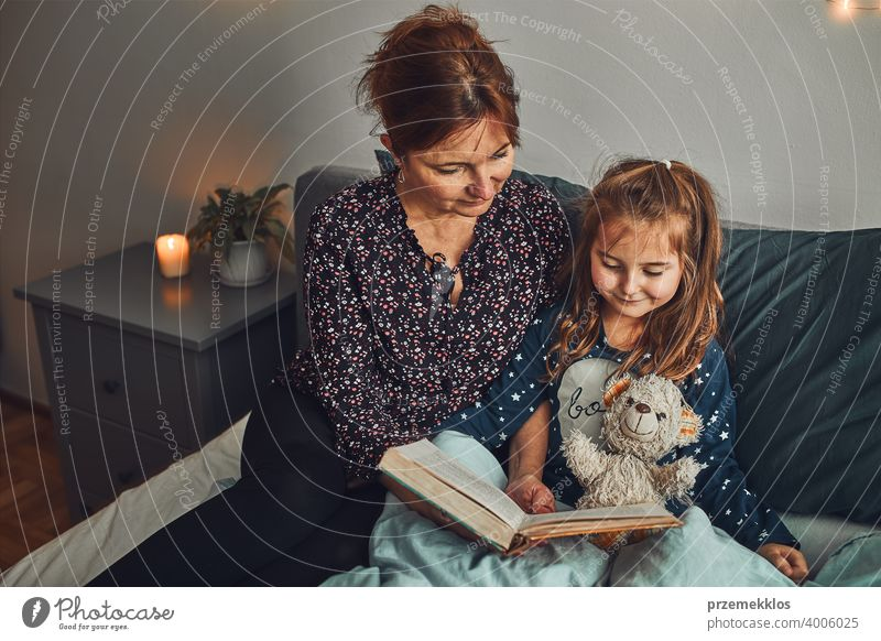 Mother reading book her daughter in bed before going to sleep. Bedtime stories for child night mother bedtime family home literature woman bedroom fairy parent