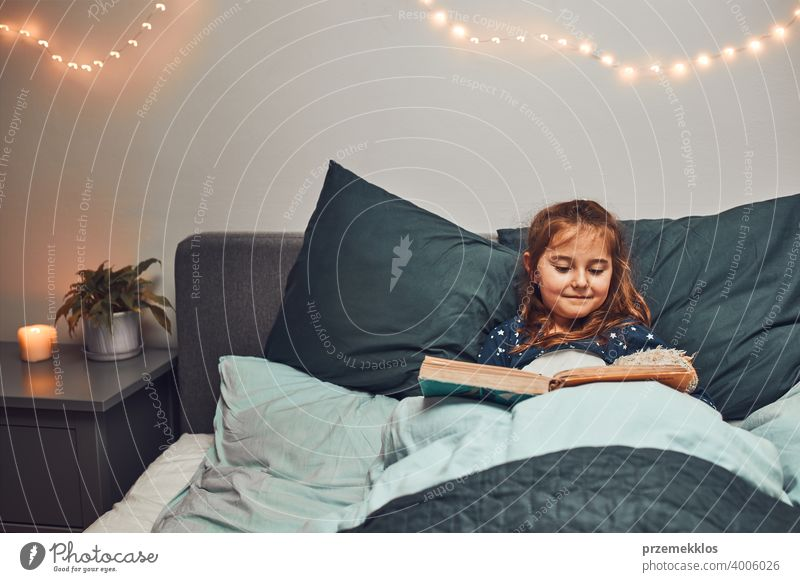 Little girl reading book and watching pictures in bed before going to sleep. Bedtime stories for child night bedtime family home literature bedroom fairy story