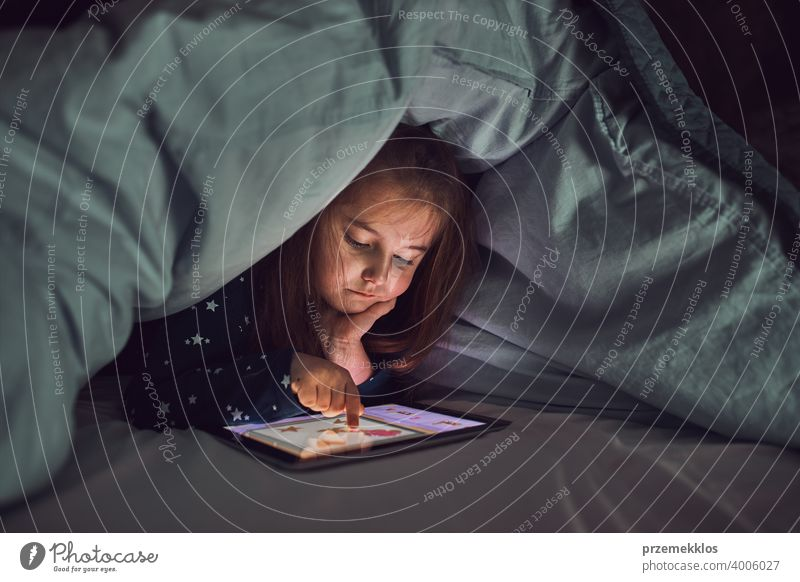Little girl having fun watching, playing and listening to stories on tablet computer laying under duvet night bedtime child home bedroom read kid relaxation
