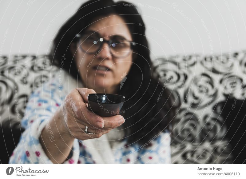 Middle-aged woman with eyeglasses and dressing gown watching news on TV. Isolated at home due to the virus. remote control television middle sofa changing