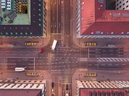 Aerial shot of an urban crossing road in a city with bend of cars from a top down view at the street between houses. turn motion traffic dynamic authentic
