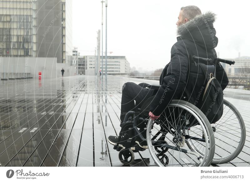 Concept of disabled person. A man in a wheelchair outside in the street. medical paraplegic disability equipment handicapped transportation mobility