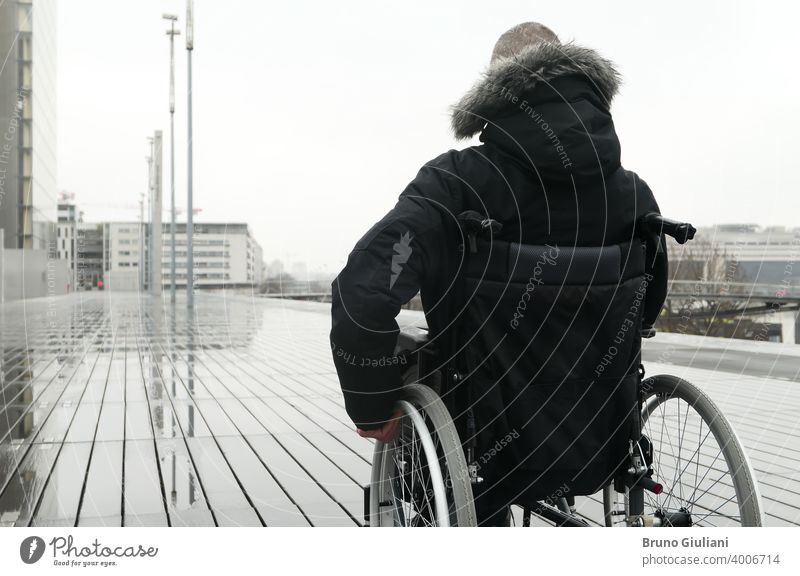 Concept of disabled person. Man in a wheelchair outside in the street. man paraplegic disability equipment handicapped transportation mobility accessibility