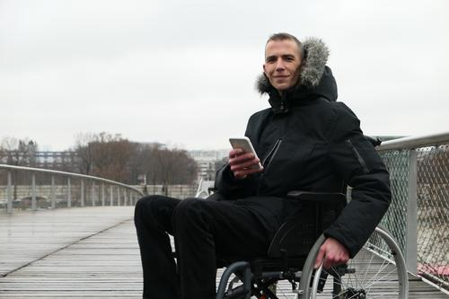 Concept of disabled person. Man in a wheelchair outside in the street. People using technology with smartphone. man equipment paraplegic connected assistance
