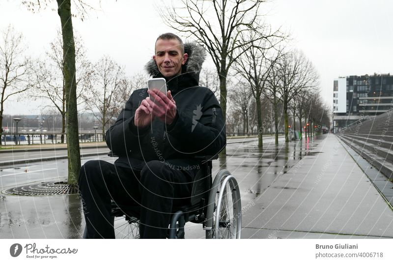 Concept of disabled person. Man in a wheelchair outside in the street in front of stairs . People using technology with smartphone. man disability equipment