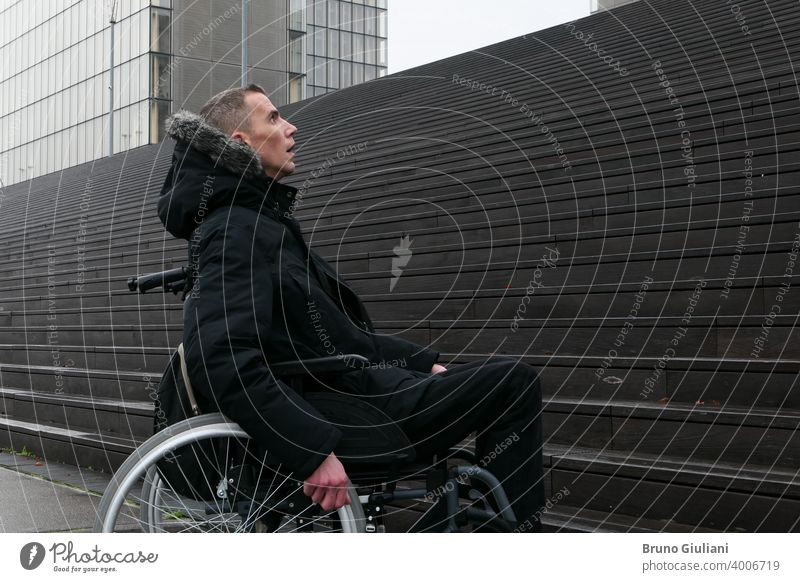 Concept of disabled person. Man in a wheelchair outside in the street in front of stairs. man disability handicap handicapped difficulty equipment accessibility