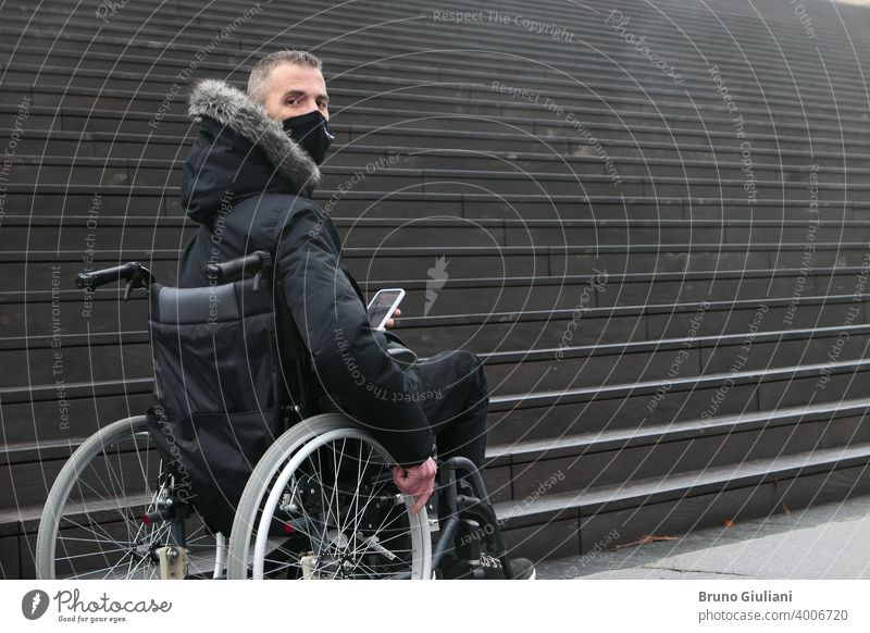 Concept of disabled person. Man in a wheelchair outside in the street in front of staircase. People with smartphone. surgical mask man accessibility disability