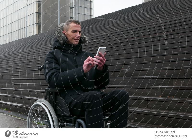 Concept of disabled person. Man in a wheelchair outside in the street in front of stairs. People using technology with smartphone. man disability equipment