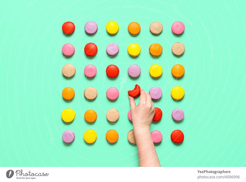Macarons symmetric aligned on a colored background. Woman hand taking a macaroon, top view above view almond cookies artisanal assortment bakery bite