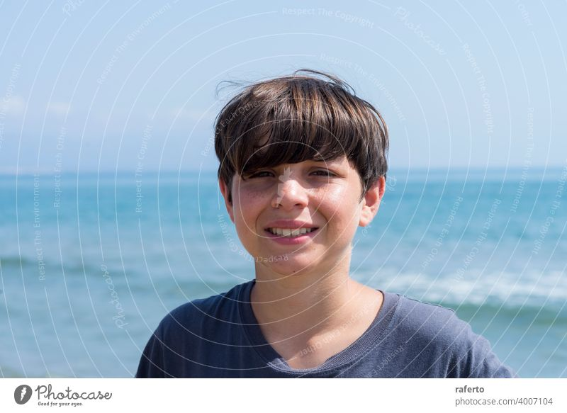 Portrait of a smiling male teen against blue sea caucasian portrait adolescence lifestyle beach young youth 1 person cute teenage hair summer boy cheerful