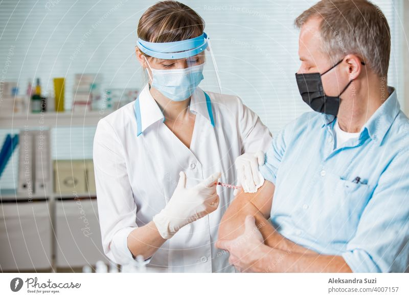 Female doctor with surgical mask and in gloves giving vaccine injection to man in hospital. Vaccination during COVID-19 pandemic arm care clinic coronavirus