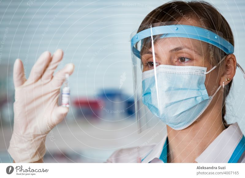 Female doctor with surgical mask and in gloves holding vaccine ampoule and syringe. Vaccination during COVID-19 pandemic arm care clinic coronavirus covid-19