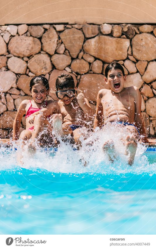 Children splashing water at the edge of the pool activity blue boy brother caucasian child childhood children cute day enjoy family friends fun goggle happiness