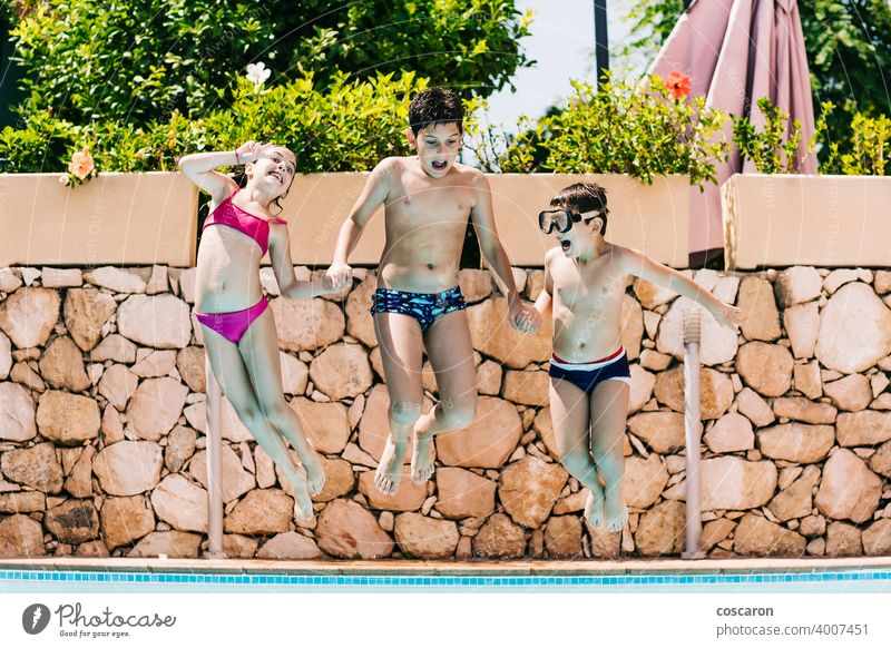 Three kids jumping into a pool action active blue child childhood children playing children vacations copy space cute dive enjoyment family friends fun girl