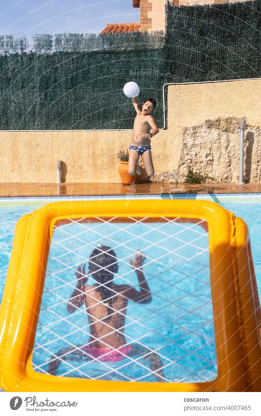 Two kids playing with a ball on a pool active activity aquatic beach blue boy caucasian child childhood children energy family fun game girl goal guy happy