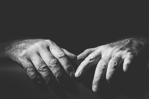 two relaxed hands lying next to each other adult black black and white bright bw closeup contain contrast dark embrace expression finger gesture grab hold
