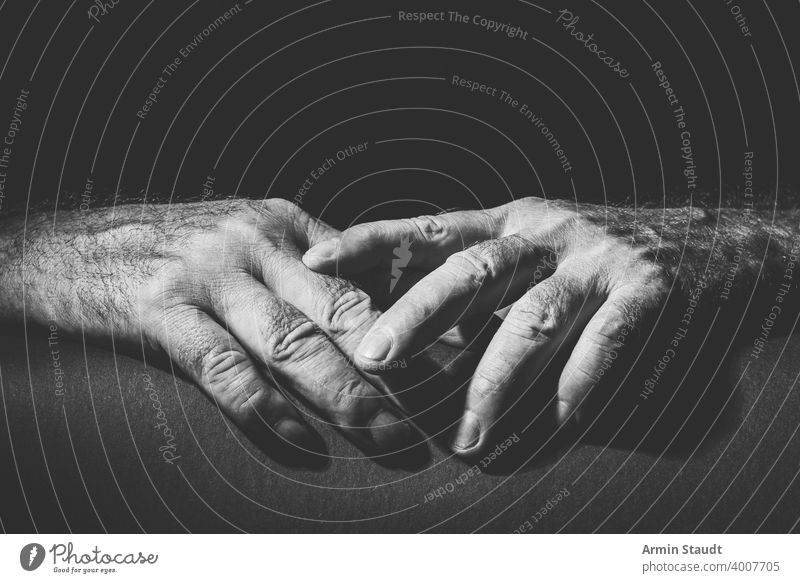 two relaxed hands lying on top of each other adult black black and white bright bw closeup contain contrast dark embrace expression finger gesture grab hold