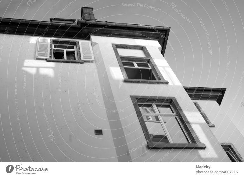 Facade of an old building from the frog perspective in a backyard in summer sunshine in the Westend of Frankfurt am Main in Hesse, photographed in classic black and white